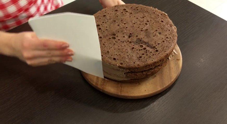 Торт Прага: Оставшимся кремом смазываем бока торта, скрывая все неровности.