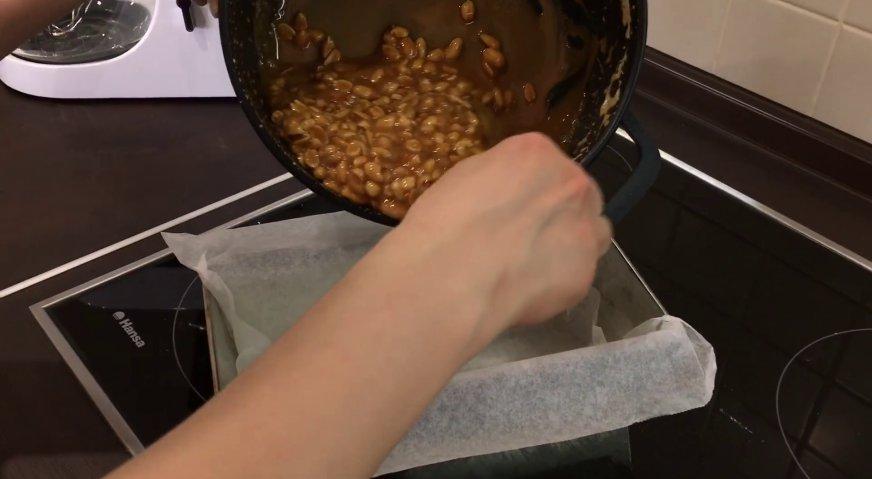 Торт сникерс: Дно прямоугольной формы смазываем маслом. Застилаем форму пергаментом, и выливаем в неё орехово-карамельную массу.