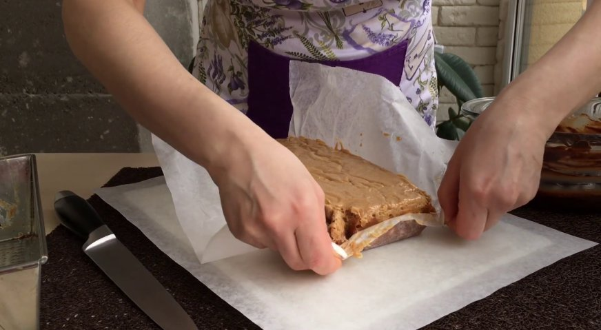 Торт сникерс: Вынимаем застывшую массу из формы, и снимаем пергамент.