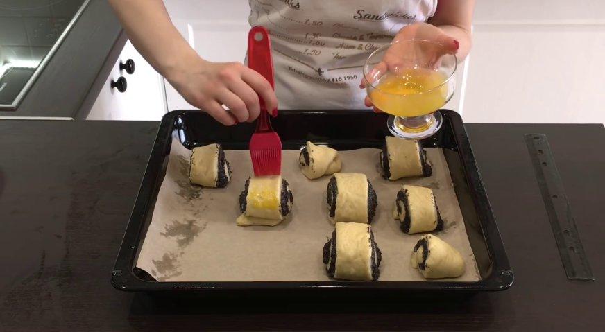 Булочки с маком: Перекладываем булочки на застеленный пергаментов противень на расстоянии друг от друга. Поверхность булочек смазываем яичным желтком.
